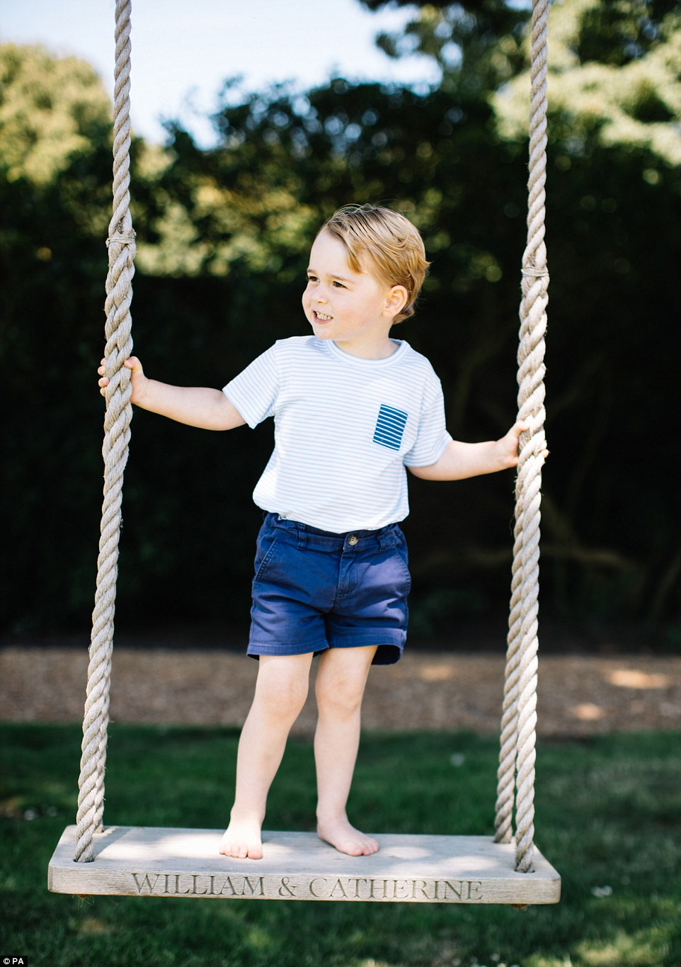 The little prince, third in line to the throne, can be seen in two shots playing on a swing in casual shorts and a T-shirt at his parents' country home that is inscribed with their names, William and Catherine. It is believed to have been a wedding gift to the couple