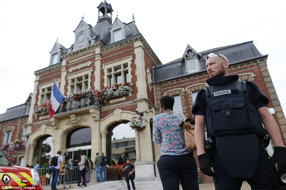 This morning it emerged Saint-Etienne-du-Rouvray was one of a number of Catholic churches on a terrorist 'hit list' found on a suspected ISIS terrorist. Police stand on guard in the town