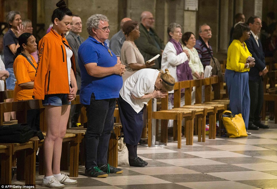 Mourners and worshippers attend a mass in memory of the slain priest, as it emerged that his killers were already known to be terror threats by French police