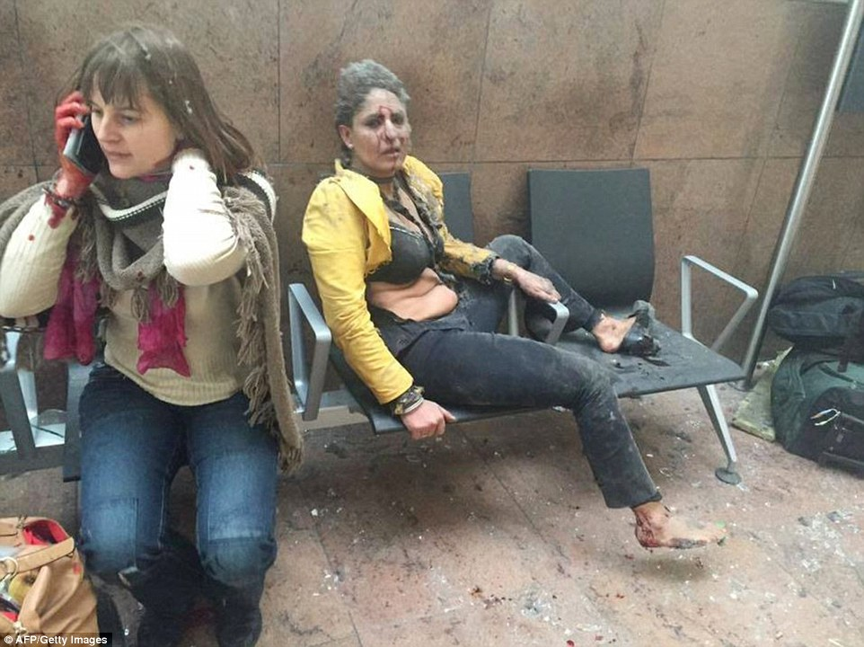 An injured woman looks on as another speaks on her mobile phone following twin blasts at Brussels airport in Zaventem on March 22