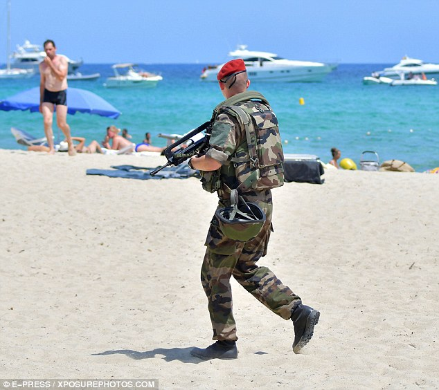 A police looks out towards sun-worshippers and the pristine blue sea of the Cote d'Azuras he patrols the beach