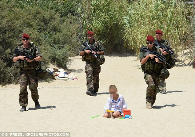 Three armed officers walk in formation as a young girl enjoys herself with a bucket and spade on the beach at St Tropez