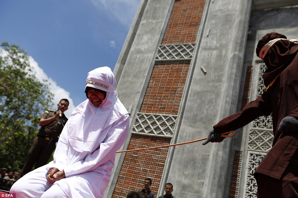 Harrowing pictures show one woman crying out as she is repeatedly lashed with a cane at Al Furqon Mosque in the city of Banda Aceh, Indonesia