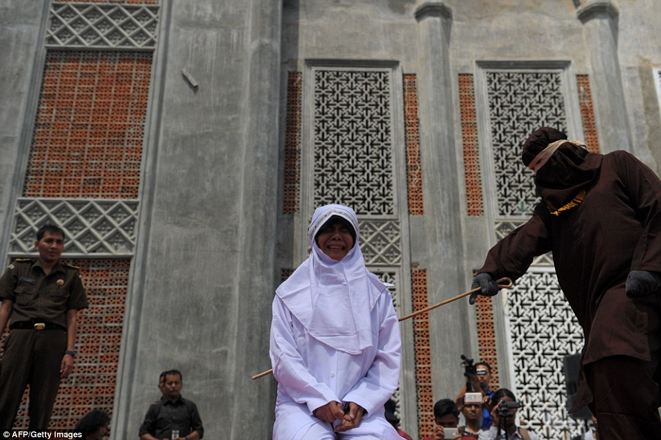 A woman cries out in agony as she is caned in public by a religious officer outside a mosque in the Banda Aceh province