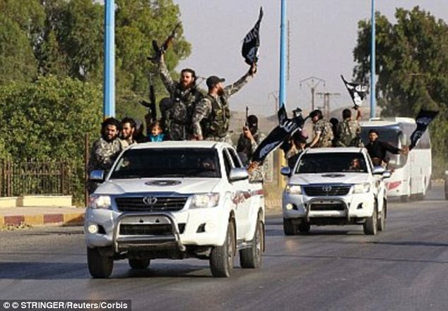 Supporters: Islamic State fighters wave flags along the streets of Syria's northern Raqqa after the group seized the city in 2014