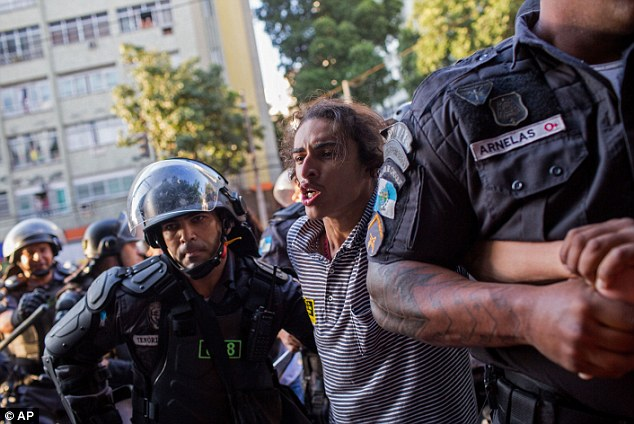 Police officers detain a man during a protest outside Maracanã Stadium, where furious mobs were tear gassed by cops