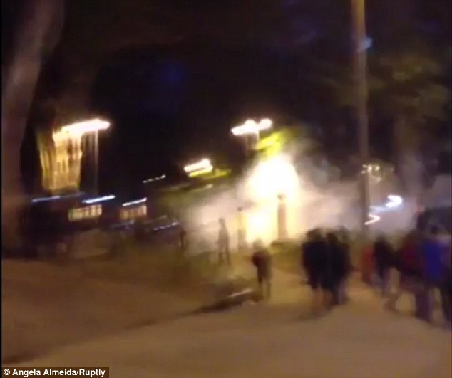 Tear gas bombs explode near demonstrators in Rio, dispersing the crowd as police move in