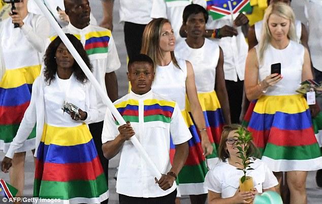 boxeador de Namibia Jonas Jonas Junias, llevando la bandera de su país en la ceremonia de apertura olímpica.  Ahora ha sido detenido como sospechoso de violación en la Villa Olímpica