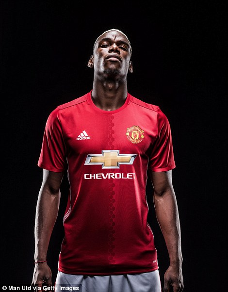 Paul Pogba poses in a Manchester United shirt for the first time since returning after completing his move on Tuesday night