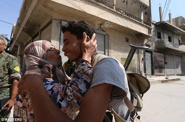 Una mujer se acerca a un luchador Fuerzas Democráticas Siria (SDF) para darle un beso después de que los combatientes entraron en Manbij, Siria, el 7 de agosto