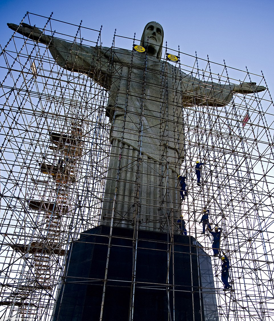 Workers climb the scaffolding surrounding the Christ the Redeemer statue during the March 2010 cleaning operation