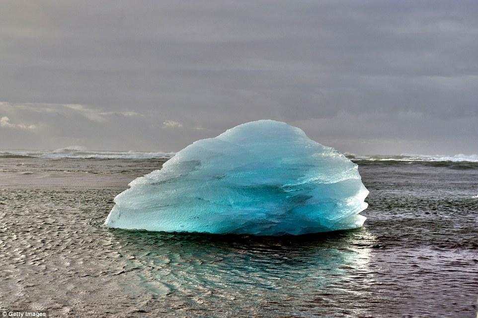 An iceberg resting atop the glassy Jökulsárlón  glacial lake in southeast Iceland, on the edge of Vatnajökull National Park