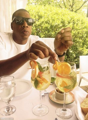 Dad in charge: Jay Z was seen in a white t-shirt swirling fruit around in glasses of white sangria as he dined with his wife and daughter