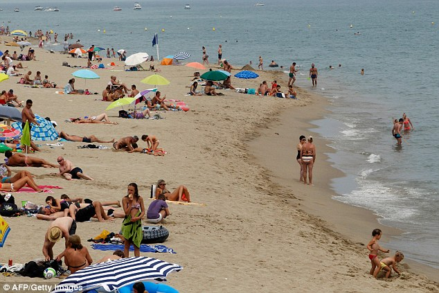 People sunbath and swim at a beach in Leucate, where the burkini is prohibited by an order of the mayor