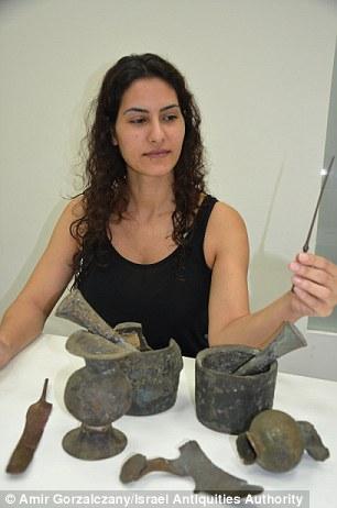 Um funcionário da Autoridade de Antiguidades de Israel examina os achados