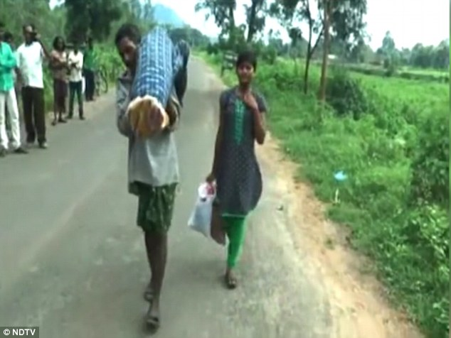 Dana Majhi was filmed with his wife over his shoulders wrapped in sheets and his heartbroken teenage daughter by his side as he headed towards his home