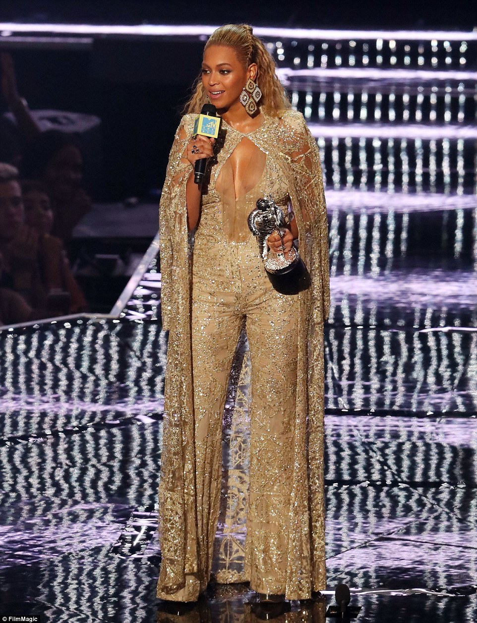 Shimmering: Beyonce looked fantastic in a gold number including jumpsuit and cape