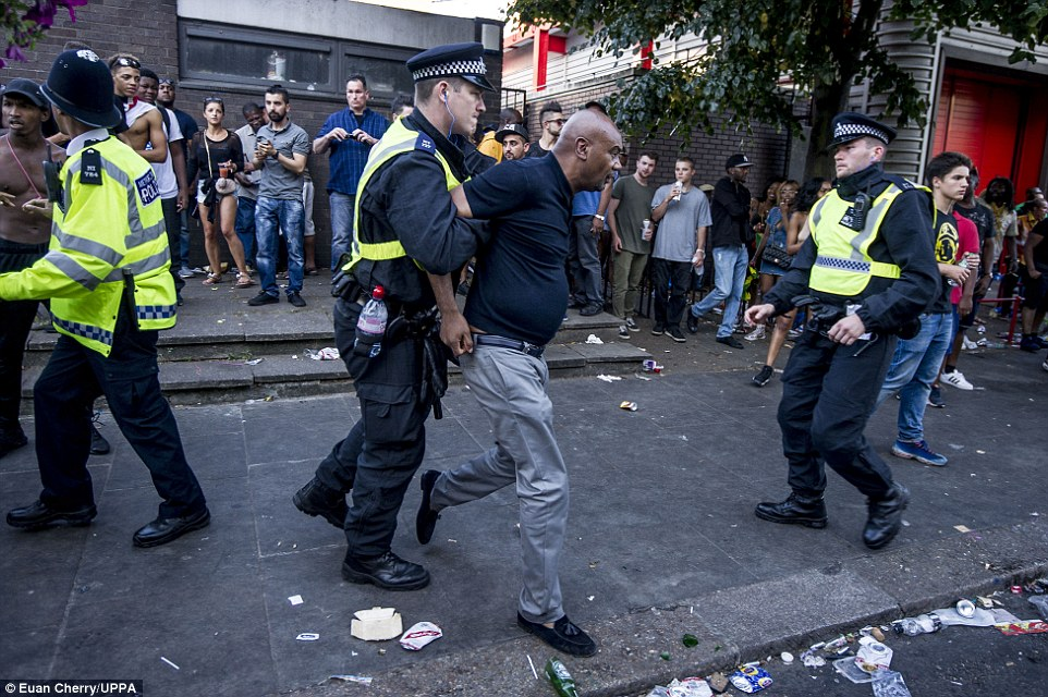 Un oficial de policía consiguió agarrarse a un hombre después de la pelea comenzó en la calle en el carnaval de Notting Hill en Londres
