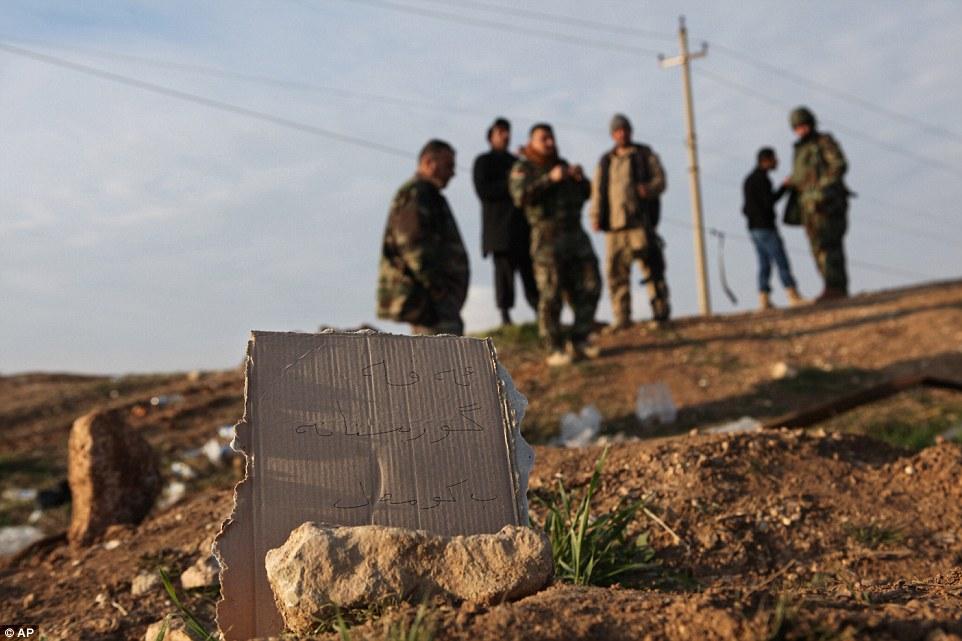 fuerzas Peshmerga kurdos inspeccionar una zona marcada en kurdo con una lectura de la muestra, 'fosa común kurda,' en el pueblo de Hardan en el norte de Irak hace dos años.  Un puñado de Yazidis que huyó de esta pequeña aldea del norte de Irak cuando invadió ISIS que en agosto de 2014 tienen de regresar después de combatientes kurdos expulsó a los extremistas