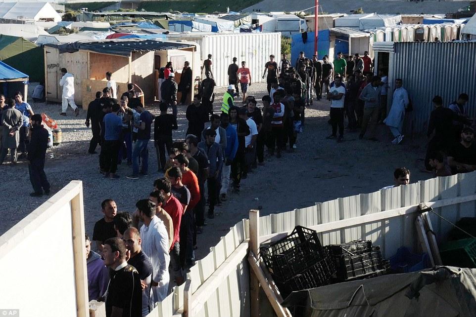 Los migrantes hacen cola para recibir su distribución diaria de alimentos en un campamento improvisado en Calais, al norte de Francia la semana pasada