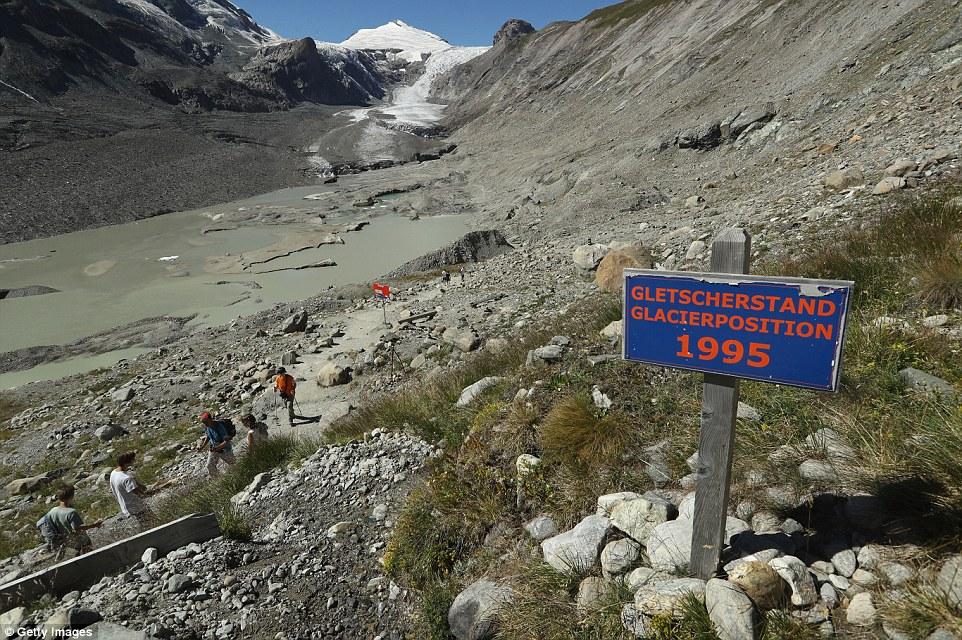 Segni di legno lungo un sentiero mostrano i luoghi dove il bordo del possente ghiacciaio Pasterze aveva un tempo sorgeva (nella foto).  L'immagine sopra mostra la sua posizione nel 1995 e dove ora siede in lontananza