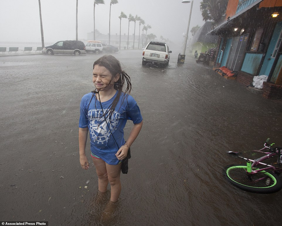 Hannah Coles, 9, takes a break from riding her bicycle through the ankle-deep floodwater as the wind whips her face in Gulfport, Florida