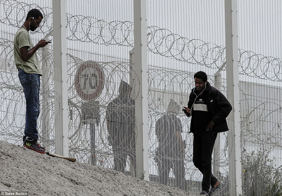 Barrier: Two migrants at the two-mile long fence that guards the port of Calais in the north of France