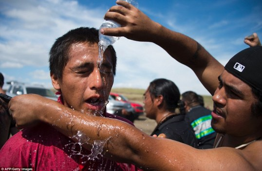 A man pours water over the eyes of a protestor after he was pepper-sprayed by security guards at a work site for the Dakota Access Pipeline