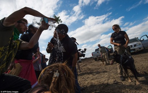 Protesters help wash out the eyes of a man after he was pepper sprayed in the face by security guards at the construction site