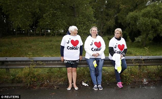 Tres mujeres se sientan a un lado de la carretera antes de formar la cadena humana que lleva 'Me encanta Calais' camisetas