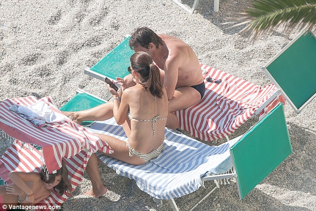 The married couple look at a phone from their sun beds during their holiday inSavona