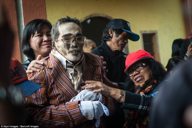 Relatives carefully dress a dead man in fresh clothes before reburying him on the island of Sulawesi in Indonesia