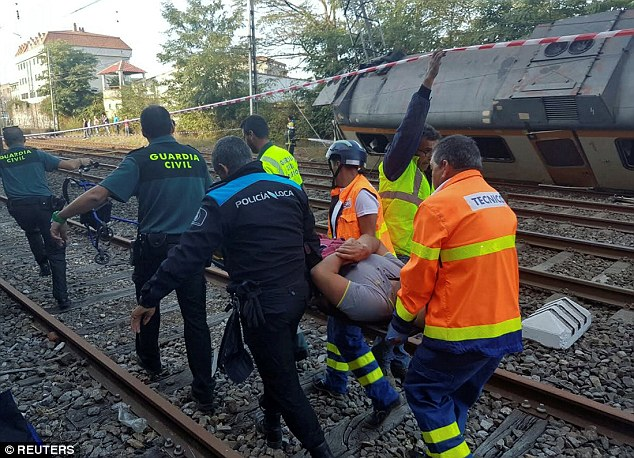 Policemen and workers carry an injured person at the scene of a train that derailed in Galicia in north-western Spain, close to the town of O Porrino