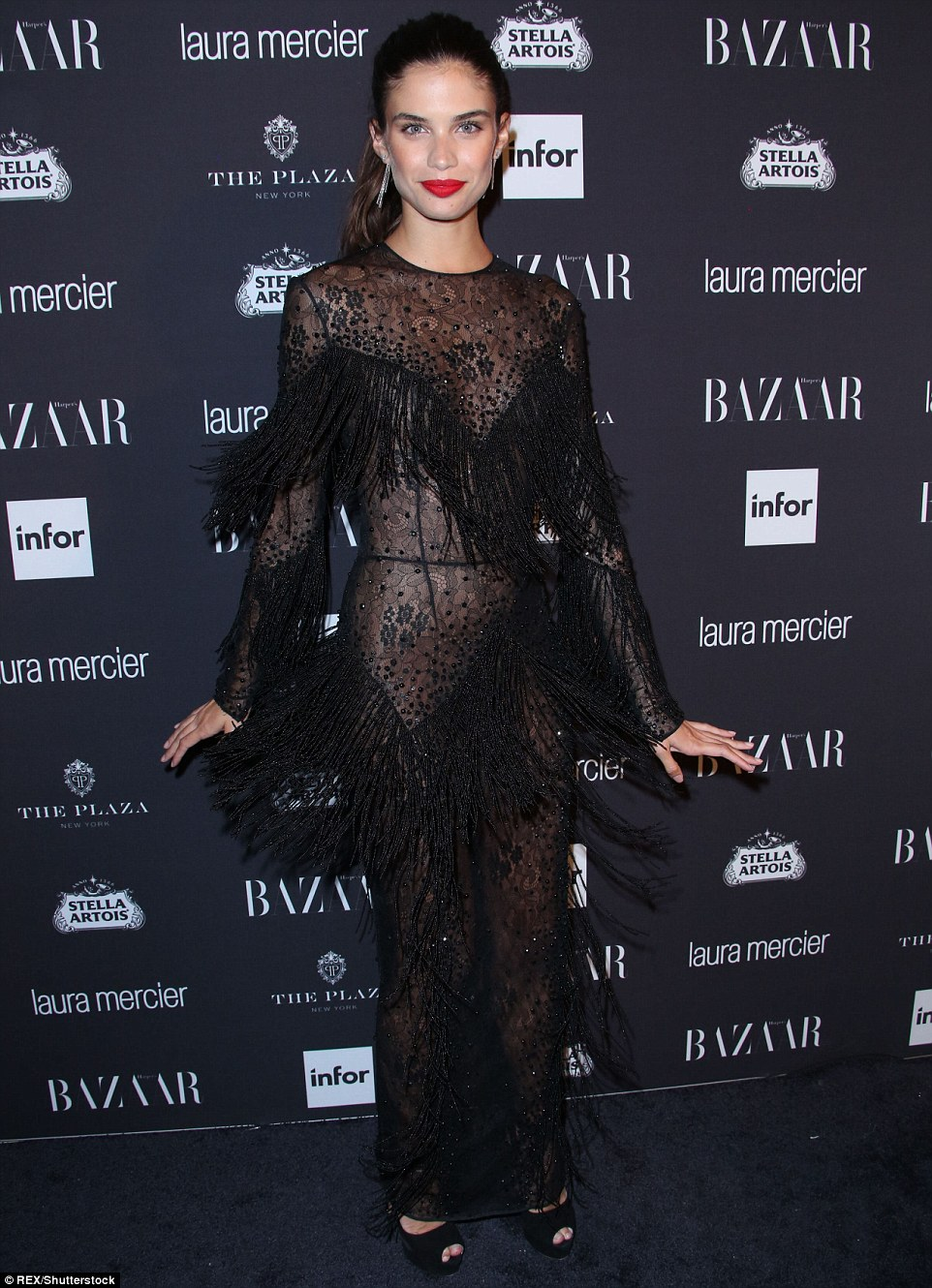 Having a blast: Sara Sampaio wore a black fringed dress with sheer elements, adding bold red lipstick