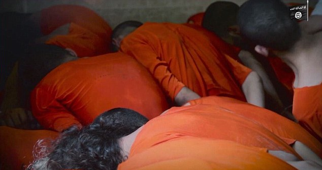 The executioner can be seen brandishing a huge knife as prisoners, dressed in orange, are bundled into the slaughter house with their hands tied behind their back