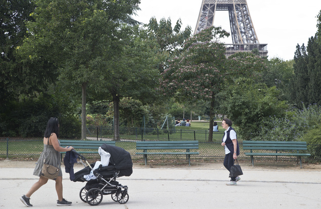 People stroll in the Champ de Mars garden near the Eiffel Tower, beside the spot where a woman was allegedly raped earlier this week,  in Paris