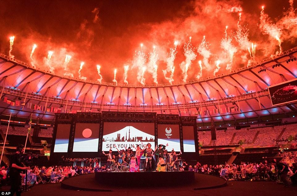 """Transferência: Uma placa dizendo """"vê-lo em Tóquio"""" aparece atrás Koichi Omae e quatro dançarinas são acompanhado no palco por GIMICO, Aya Sato e Bambi caminhando triunfantemente até o encontro pista em torno de Akira Hiyama durante a cerimônia de encerramento dos Jogos Paraolímpicos Rio 2016"""