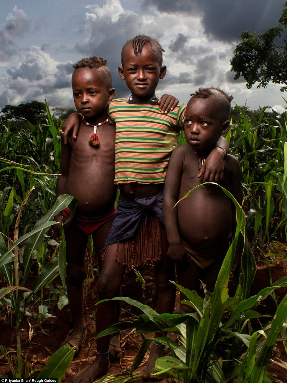 An older boy throws his arms around two younger boys in tribal wear as they pose in the long shrubbery of Ethiopia in this shot