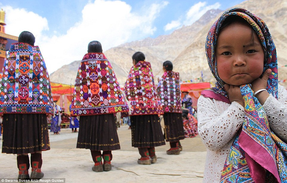 Runner up: An adorable young girl adorned in a vibrant head scarf stands before women in local costume in the mountains