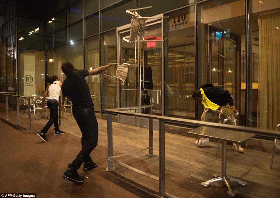 The peaceful march turned ugly and protesters are pictured, above, throwing chairs at a restaurant during the demonstration