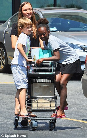 Zaraha Jolie-Pitt and brother Knox Jolie-Pitt are pictured holding on to a shopping cart