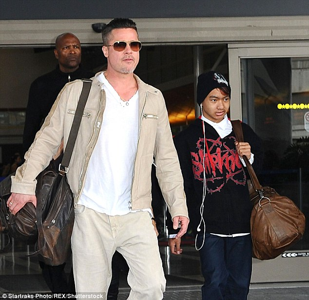 No truth:A friend of Brad Pitt's is denying a report that claims the actor lunged at his son Maddox while they argued on a flight last week (Pitt and Maddox in 2014 above)