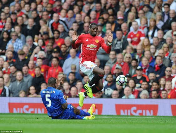 United's world record signing Paul Pogba hurdles a slide challenge from the Leicester captain Wes Morgan