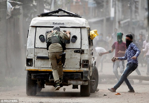 Kashmiri demonstrators hurl stones at an Indian police vehicle during a protest in Srinagar last month