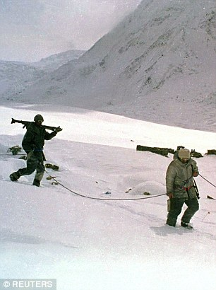 Pakistan soldiers, tied to each other for safety in hostile weather conditions, carry their weapons as they cross the Siachen Glacier