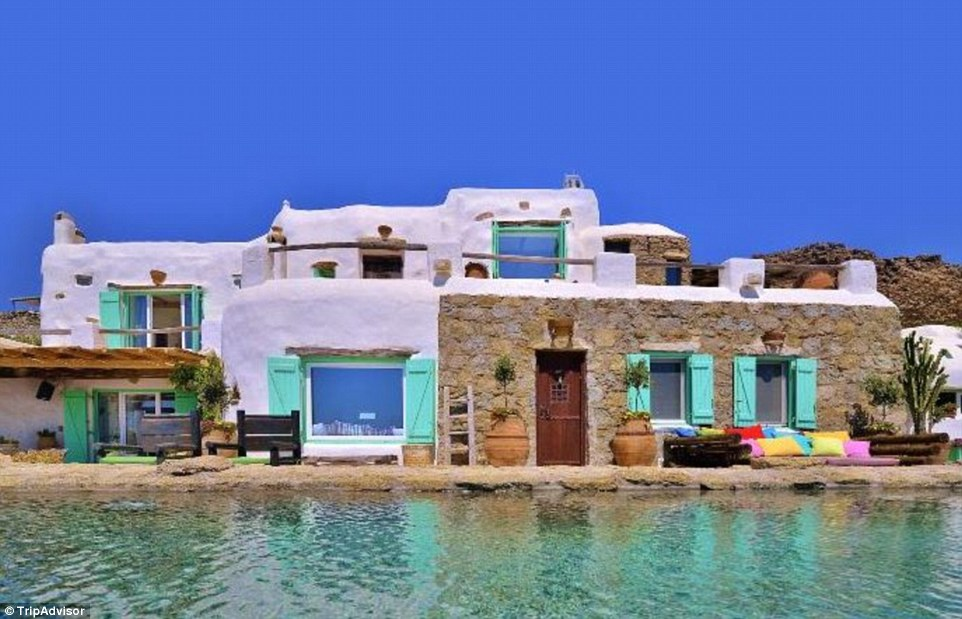 Colourful accents at the Mykonian Passion villa light up its white stone exterior, which is fronted by a 20m-long infinity pool