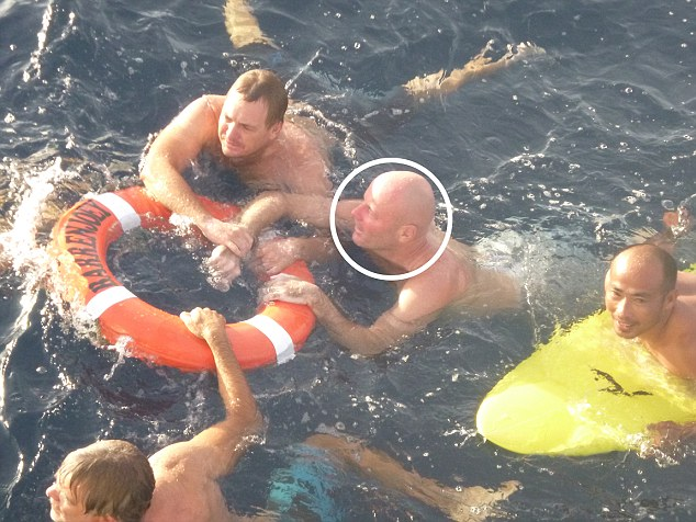 Brett Archibald (circled) described how fell overboard in the dark without a life jacket during a boat trip off Indonesia. Pictured, Brett being towed to the Barrenjoey