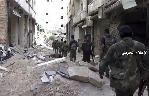 In this still image taken from video provided by the Syrian government-controlled Syrian Central Military Media, government troops patrol inside the Bustan A...