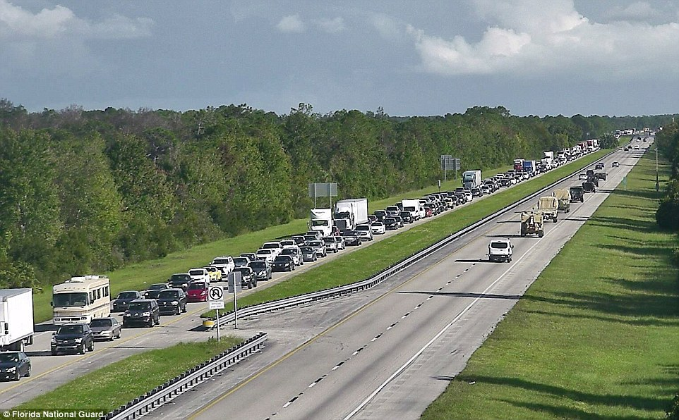Traffic as far as the eye can see: Thousands of families have been caught in gridlock across the state and up the East Coast into the Carolinas and Georgia, as they flee their homes ahead of the storm - while the National Guard trucks drive towards the evacuation zones to assist