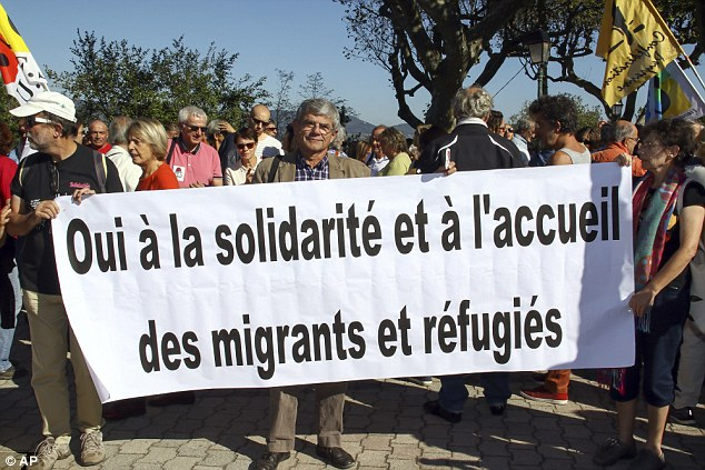 Left-wing activists hold a banner reading: 'Yes to solidarity and welcome to migrants and refugees' in Pierrefeu